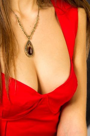 tetas: tetas chica. pechos femeninos cubiertos con un vestido rojo