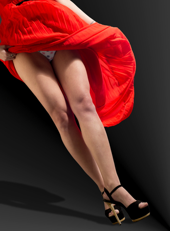 red pants: Legs, red pants, black high-heeled shoes, red dress, the wind picked up the dress visible panties, ??? Stock Photo