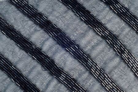 owing: Fabric Color black with beads.  Photography Studio. texture. ebon, sable, smutty. of the very darkest color owing to the absence of or complete absorption of light; the opposite of white