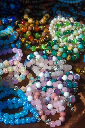 threading: female beads. a small piece of glass, stone, or similar material, typically rounded and perforated for threading with others as a necklace or rosary or for sewing onto fabric.