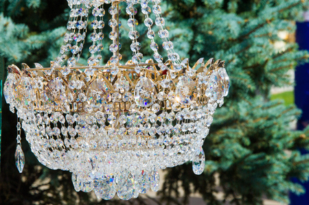 geometrically: crystal chandeliers. a piece of a homogeneous solid substance having a natural geometrically regular form with symmetrically arranged plane faces.
