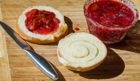 smeared: breakfast with jam from plums. Muffin smeared plum jam. A knife for cutting bread buns Stock Photo