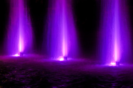 Fountain jet of fluid ejected upward from the pipe holes or the pressure force. Lumiere fountain. rhythmic light effects