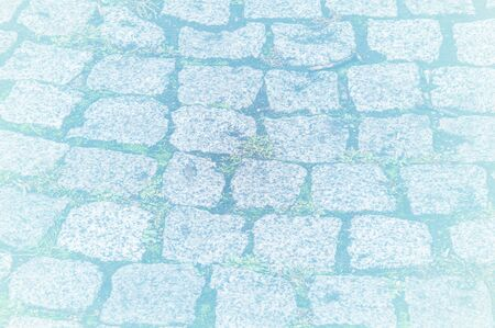 cobblestone road: texture, background. The pavement of granite stone. Paved roadway street. any paved area or surface. Old cobblestone road pavement texture, grass between stones