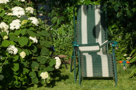 typically: portable chair in the garden, comfortable chair, typically upholstered, with side supports for a persons arms.