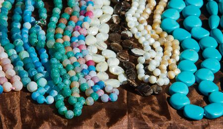 perforated: female beads. a small piece of glass, stone, or similar material, typically rounded and perforated for threading with others as a necklace or rosary or for sewing onto fabric.