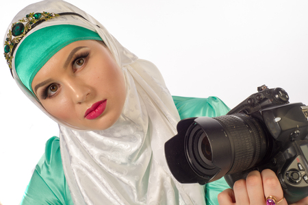 interraction: A woman in a hijab, holding a camera