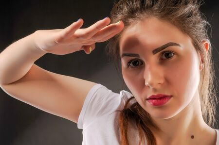 Portrait of a girl salutes military rules. Attractive business woman saluting over Stock Photo