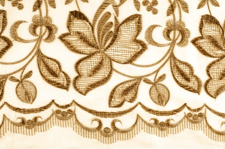 texture lace. a fine open fabric, typically one of cotton or silk, made by looping, twisting, or knitting thread in patterns and used especially for trimming garments. Stock Photo