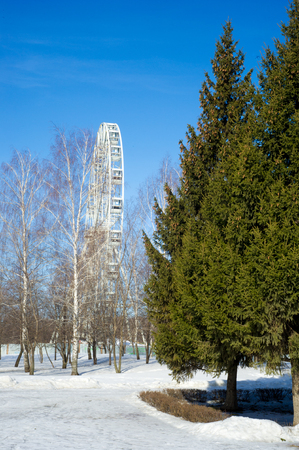 Park in the spring, packed snow, ferris wheel