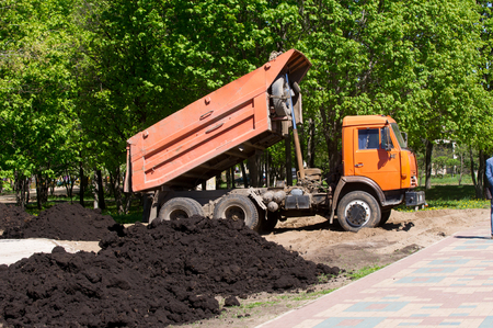 hauler: car dumper unloads the black earth on the flowerbed in city park Stock Photo