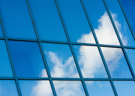 Texture, pattern, background. Reflection in building windows. Blue windows, clouds reflected in the windows