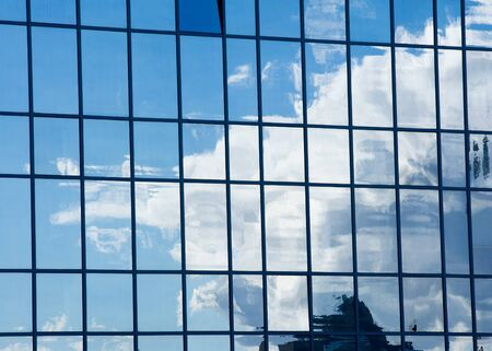futuristic city: Texture, pattern, background. Reflection in building windows. Blue windows, clouds reflected in the windows