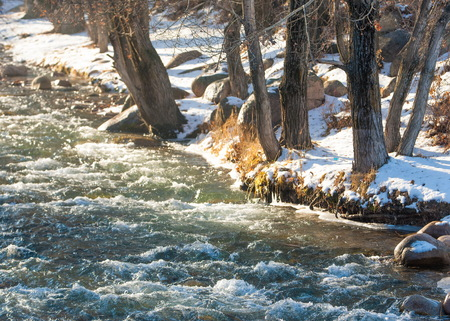 cascade: Streaming water in a small river at early springtime. Spring scene.  Mountain landscape with a frozen creek