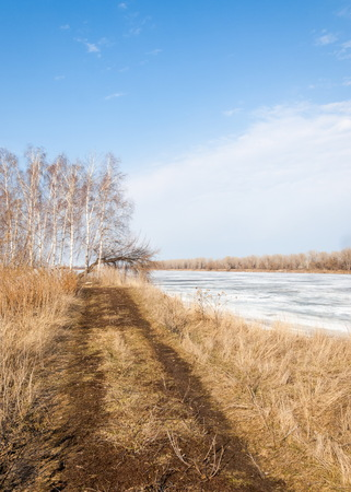 Spring River, the ice on the river. picturesque spring landscape with river ice melted bare trees and beautiful clouds in the blue sky