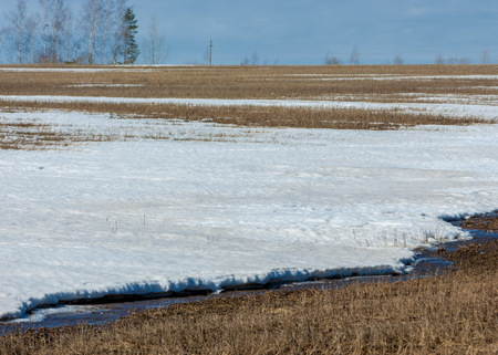 cascade: early spring grain stubble of mown old packed snow, streams of water. blue sky Stock Photo