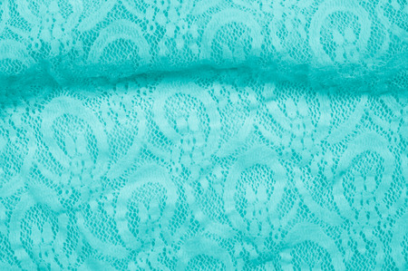 specially: Texture, fabric, background. Lacy turquoise fabric, lace. A thin open fabric, usually cotton or silk, made by a loop, twisting or knitting on patterns and is used specially for trimming clothes. Stock Photo