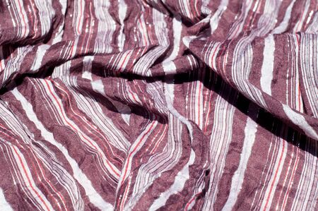Texture, background, pattern. Female striped scarf, cloth striped brown, white, red with glitter