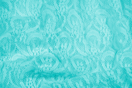 Texture, fabric, background. Lacy turquoise fabric, lace. A thin open fabric, usually cotton or silk, made by a loop, twisting or knitting on patterns and is used specially for trimming clothes. Stock Photo
