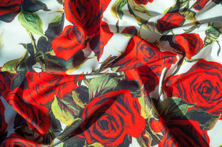 Texture, background, pattern. Cloth Silk Abstract Pattern. On the fabric are painted roses. Red roses on a white background Stock Photo