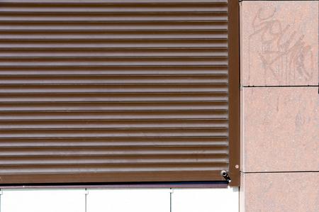 jalousie: Summer landscape, city walls, metal shutters. Front view of black metal windows. Abstract dark brown metallic background