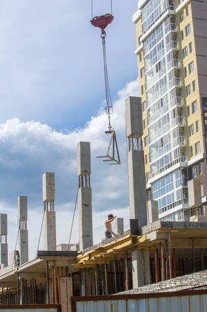 Photo of a house under construction. Building under construction. Lifting cranes and building under construction. big construction site. Construction crane above building