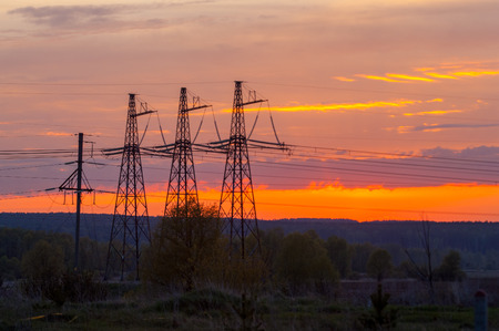 Technogenic landscape, urban. The energy of the pole in the rays of the rising sun. Posts for the transfer of high lead. Steel Electric Pillars
