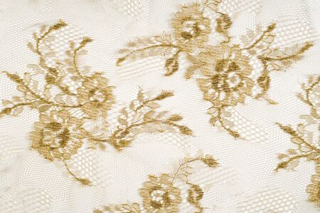 Image texture background, decorative gold lace with pattern. Golden vintage lacy background. Golden lace on white background spandex, macro. Lace decorative floral pattern.