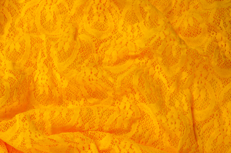 specially: Texture, fabric, background. Lacy Yellow fabric, lace. A thin open fabric, usually cotton or silk, made by a loop, twisting or knitting on patterns and is used specially for trimming clothes. Stock Photo