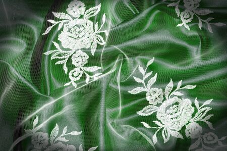 Texture, background, pattern. Lacy white fabric. Flowers made of lace fabric. Green background of silk fabric. greeting card. Wallpaper for your desktop. Screensaver backdrop for designer