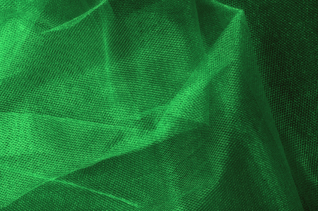 Texture, background, pattern. Green, salad color of silk fabric. Green fabric texture. Close up view of green fabric texture and background. Abstract background and texture for designers. Stock Photo