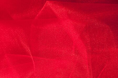 Texture, background, pattern. Red cloth. Abstract red background. Red abstract fabric background or liquid waves Illustration of wavy silk folds Stock Photo