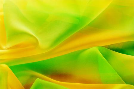 Texture, background, pattern. Silk fabric is transparent, dark orange, dark red, dark green, saturated colors.