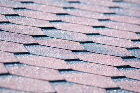 An asphalt shingle is a type of wall or roof shingle that uses asphalt for waterproofing. They are one of the most commonly used roofing covers in North America Stock Photo