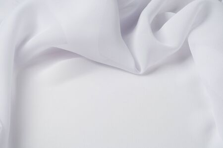 Texture, background, pattern. Silk fabric of white color, abstract folds. Smooth elegant white silk or satin texture