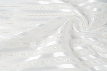 Background texture, pattern. White silk fabric, with a light strip. Closeup of rippled white silk fabric. Smooth elegant golden silk can use as wedding background.  Retro style