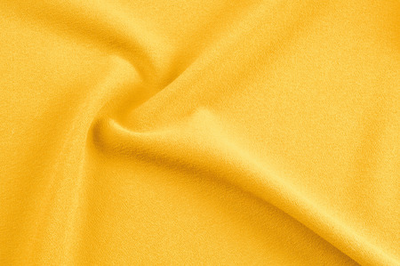 Texture, background, pattern. Yellow silk fabric.Smooth elegant golden silk can use as background. Golden satin textile background.