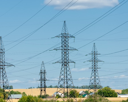 Power poles.  Row of numerous high-voltage, heavy-duty industrial pylons for electricity distribution. Parallel wires on a blue sky background. Power, energy and electricity infrastructure concept. Stock Photo