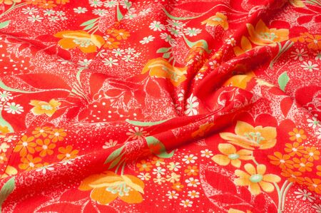 Texture, background, pattern. Cotton cloth of red color, On the fabric are painted flowers yellow white Stock fotó - 88902023
