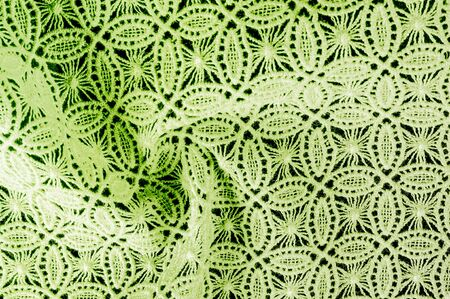 Image texture background, decorative lace with pattern.  green vintage lace background. Green lace on white spandex background, macro view. Ornamental round lace Stock Photo