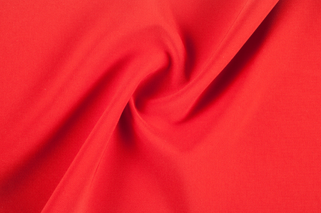 Red silk fabric. The art of seduction and catching of the eyes is depicted in this red silk Scarlet and District Mixed Satin. The glowing face shows a fat red color and a smooth, lightly brushed hand. Stock Photo