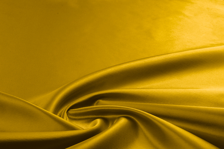 Texture, background, pattern. A yellow satin is a silk fabric. Bright yellow - Thick silk satin solid color colored luxurious silk fabric for evening dresses, Stock Photo