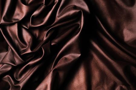 テクスチャ、背景、パターン。ダークブラウンのシルク生地。それは濃い茶色の茶色、純粋な絹の duoni です。これは美しいスカーフ、クラッチ、ネ