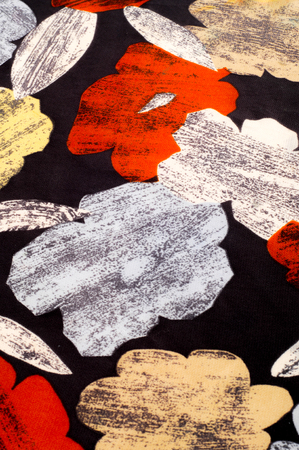 Texture, background, pattern. A womans silk handkerchief is decorated with bright colors. White yellow red flowers on a black background