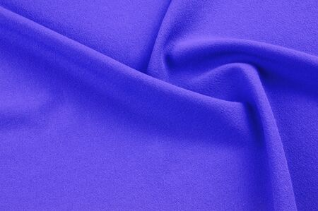 Texture, background, pattern. Lilac silk fabric. Smooth elegant lilac silk or satin can be used as a background. Luxurious lilac satin background close-up.