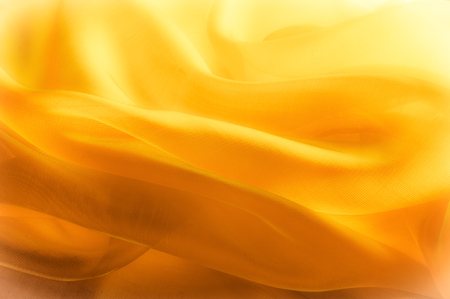 sumptuousness: The photo is blurred. Texture, background, pattern. Yellow silk fabric. Abstract background of luxury Yellow fabric or liquid wave or wavy grunge texture. The whole background.