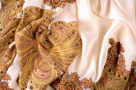テクスチャ、パターン。茶色のパターンを持つ白い絹の生地。インディアンのデザインの女性のスカーフ。他の名前の描画は甘いような香りがすることができますが、これらのパターンのシルクのようにゴージャスに見えることはありません。 写真素材 - 88909713