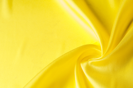Texture background pattern. Silk fabric, yellow fabric. On a black background. Flower textile or fabric. Texture of fabric. Fabric, textiles, fabric, material, woven.