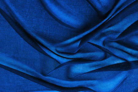 Texture, background, pattern. Blue transparent fabric. Crystal organza has a grainy shine and feel compared to the mirror organza, which has a smoother shinereflection and feel.