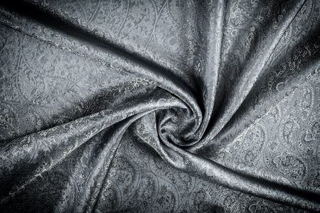 Background texture, pattern. Gray Paisley Silk Jacquard is an intricately woven shiny fabric with a tonal design woven in. The weave creates the effect of a shadow pattern or print. Stock Photo